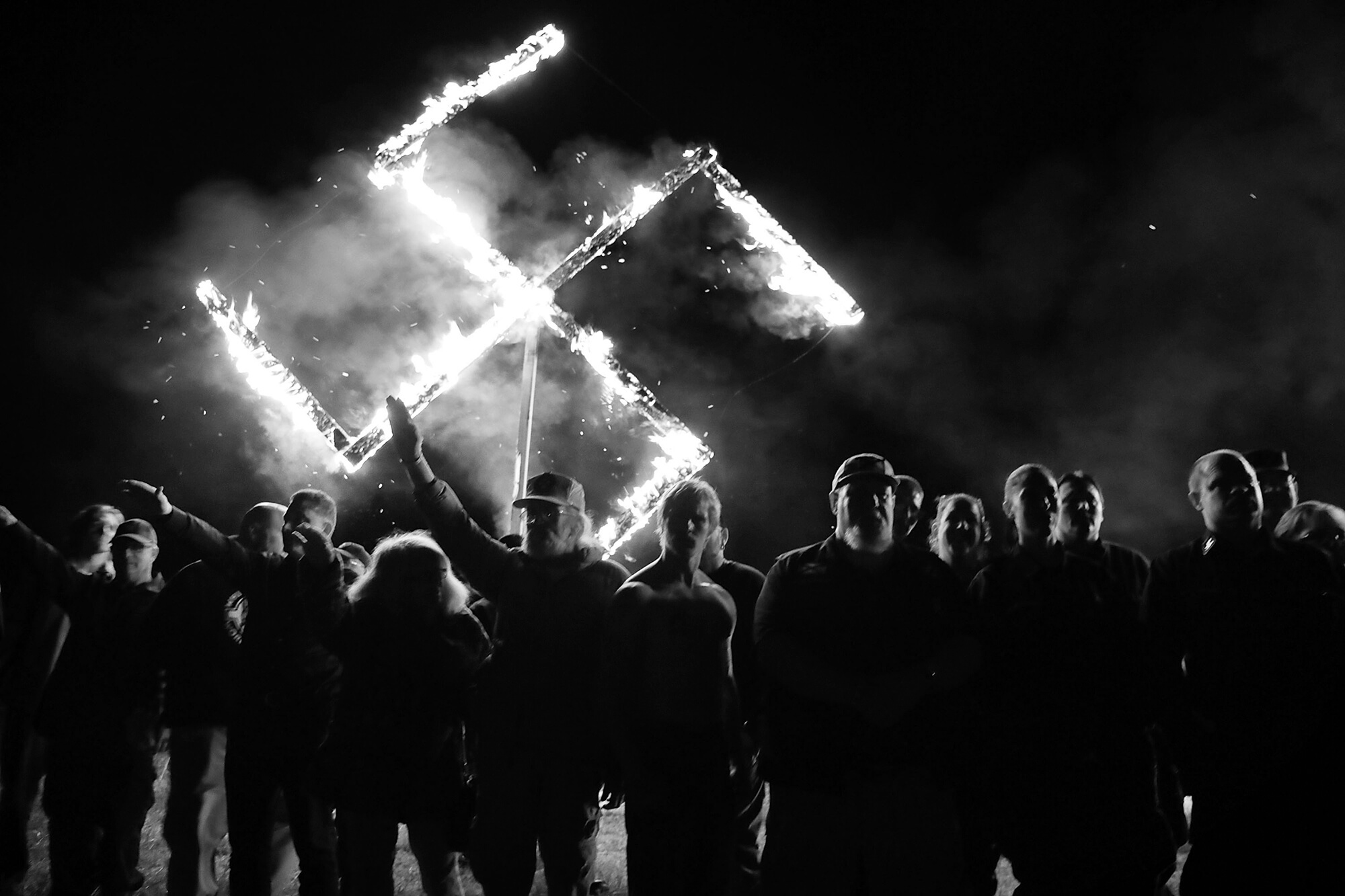 Members of the National Socialist Movement, one of the largest neo-Nazi groups in the US, hold a swastika burning after a rally in April 2018 in Draketown, Ga. From the White House, Donald Trump ignored the danger of white supremacist groups, and equivocated on the threat they posed to American values and the homeland.Trump later went on to foment an insurrection and attempted coup with the support of white supremacist groups.